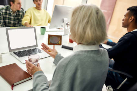 Close up of aged woman, senior intern holding, taking pills while using laptop, sitting at desk, working in modern office with other young employees