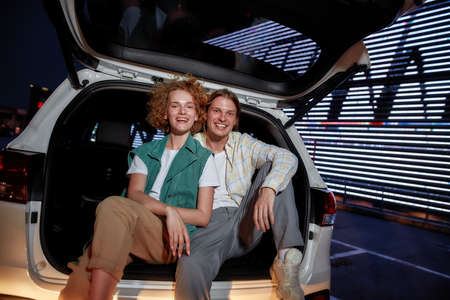 Two young casually dressed white friends of different genders smiling looking into a camera sitting in an opened car trunk outside on a parking site with a led screen behind