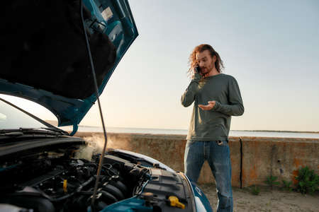 Young man talking on the phone with car service, assistance or tow truck while standing near his broken car with open hood