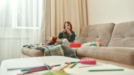 A littile girl playing with a toy sitting on a sofa having her toys around in a big bright room