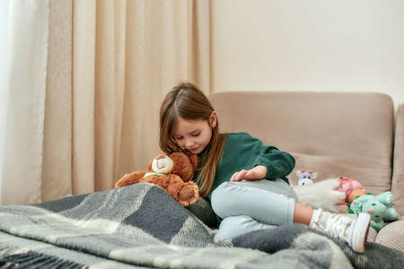 A cute little girl lying down on a sofa with a plaid and her teddybear in a bright room