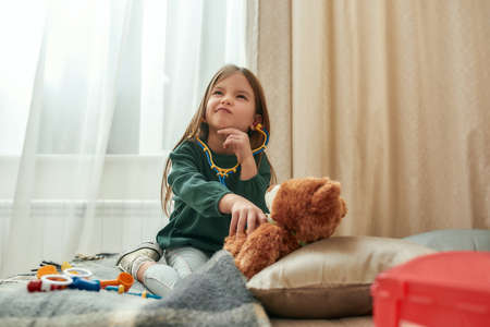 A small girl playing doctor with a toy stethoscope having a teddybear as a patient deciding what to do while sitting on a sofa in a spacy room