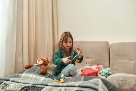 A small girl holding a toy stethoscope while sitting on a sofa with a teddybear and plaid near to her in a big bright guestroom being alone at home. Childrens leisure activities Stok Fotoğraf