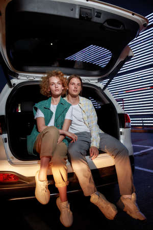 A group of two young well-dressed white friends of different genders looking into a camera sitting in an opened car trunk outside on a parking site with a led screen behind