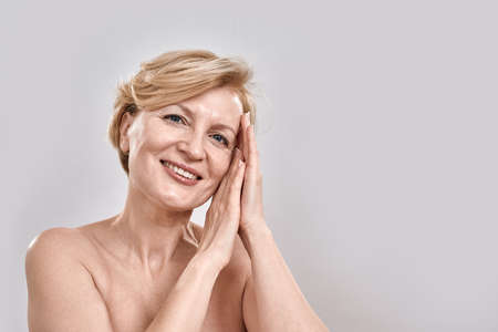 Close up portrait of beautiful middle aged woman in underwear looking at camera, showing sleep gesture while posing isolated against grey background