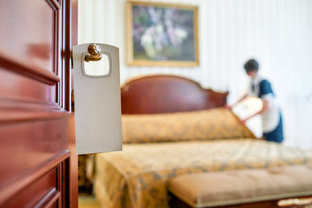 Outstanding Service. A housemaid in uniform cleaning a hotel room in the background and door with a sign at the front. Stock fotó