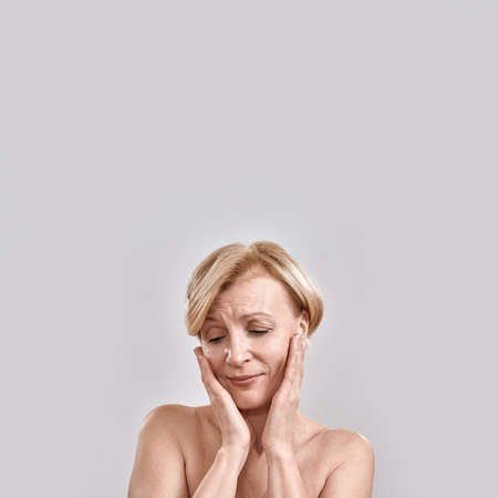 Portrait of sensitive, emotional pretty middle aged woman touching cheeks, looking down, posing isolated against grey background. Beauty, skincare concept Stock fotó
