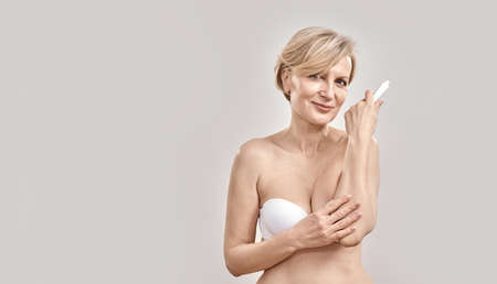 Attractive middle aged woman looking at camera, applying exfoliating moisturizing cream on dry elbow skin while posing isolated over grey background 免版税图像 - 159098598