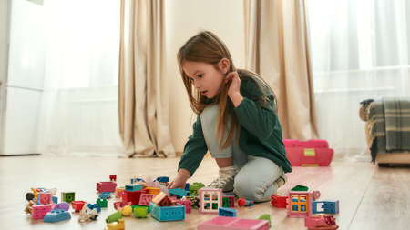 A cute little girl playing with her toys on the floor of a spacy kitchen Stock fotó