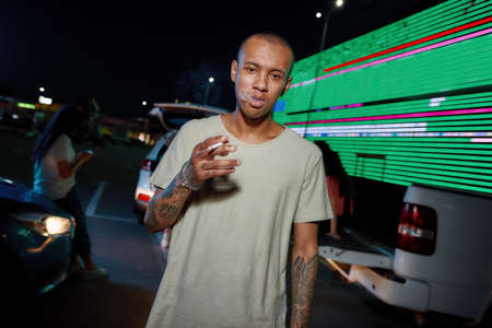 A young dark-skinned casually dressed tattooed man looking into a camera while holding a cigarette and breathing out smoke having friends and a led screen on a background Stock fotó
