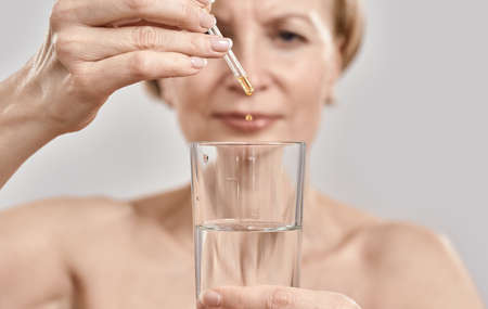 Close up of hand of attractive middle aged woman holding dropper with medication and glass isolated over grey background 免版税图像 - 159098765