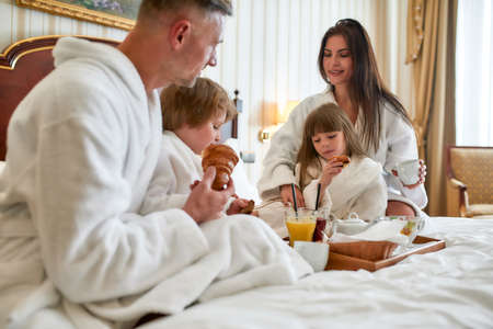 Relax and feel peace. Close up of parents and two kids in white bathrobes having breakfast in bed, eating and drinking in luxurious hotel room. Family, resort, room service concept 免版税图像 - 159098767