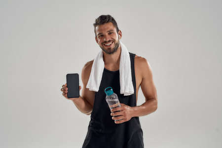 Young handsome caucasian sportsman holding smartphone and water 免版税图像 - 159098768
