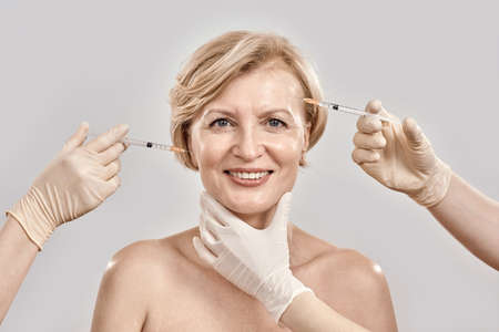 Portrait of beautiful naked middle aged woman smiling at camera while she gets injections in her face, posing isolated against grey background 免版税图像 - 159098770