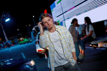 A commonly dressed young white long haired man looking into a camera standing outside combing hair with his hand having friends cars and a led screen behind 免版税图像 - 159098771