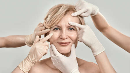 Beauty portrait of middle aged woman smiling at camera. Beautician hands in gloves checking female face skin isolated against grey background