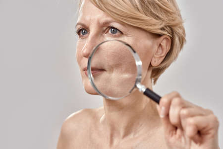 Close up portrait of attractive middle aged woman looking aside, holding a magnifying glass and showing her wrinkles, posing isolated over grey background Stock fotó