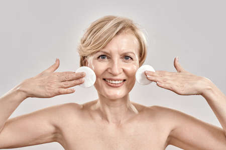 Beautiful middle aged woman with flawless skin smiling at camera while holding cotton pads near her face, posing isolated over grey background
