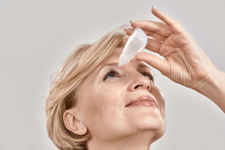 Close up portrait of attractive middle aged woman applying eye drops, standing isolated over grey background