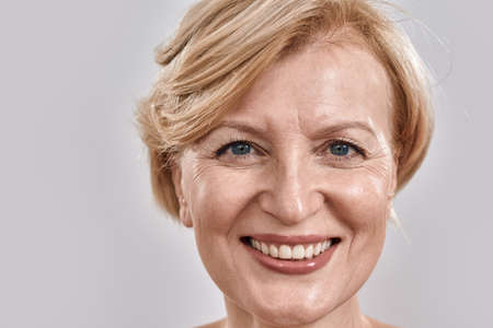 Close up shot of face of beautiful middle aged woman smiling at camera while posing isolated against grey background Stock fotó