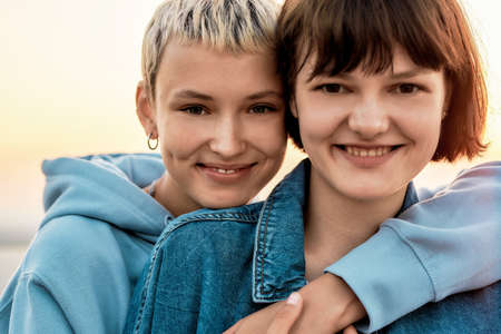 Cropped portrait of two attractive young women with short hair smiling at camera, Young lesbian couple spending time together