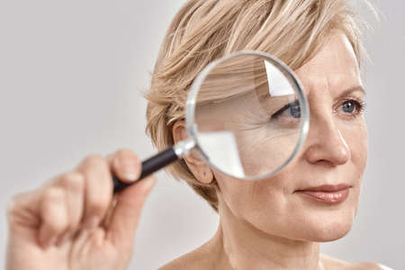 Close up portrait of attractive middle aged woman looking aside, holding a magnifying glass and showing her wrinkles, posing isolated over grey background 免版税图像 - 159098787