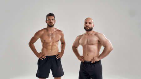 Young muscular caucasian men standing with hands on waist Stock fotó