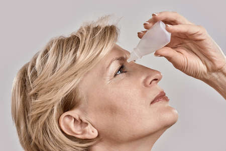Close up portrait of attractive middle aged woman applying eye drops, standing isolated over grey background 免版税图像 - 159098789