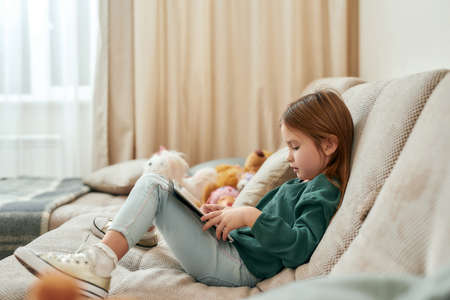 A small cute girl is into a process of playing games on a tablet while sitting on a sofa 免版税图像 - 159098791