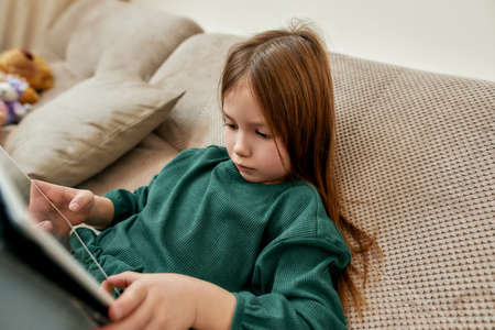 A little girl playing videogames on her tablet while sitting resting on a sofa