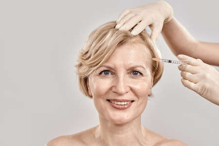 Portrait of beautiful naked middle aged woman smiling at camera while she gets injection in her face, posing isolated against grey background
