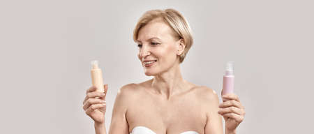 Portrait of beautiful middle aged woman holding two bottles of different cosmetic skincare products and choosing what to apply while posing isolated over grey background 免版税图像 - 159195824