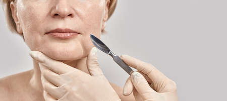 Cropped shot of face of middle aged woman and the medical scalpel in doctors hands isolated over grey background