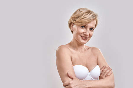 Close up portrait of attractive middle aged woman in underwear looking at camera while posing, standing against grey background 免版税图像 - 159383268