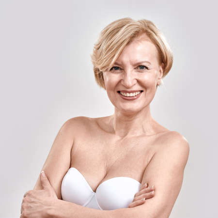 Portrait of beautiful middle aged woman in white bra smiling at camera while posing isolated against grey background