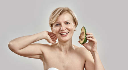 Portait of beautiful middle aged woman smiling at camera while holding half of a ripe delicious avocado, posing isolated over grey background