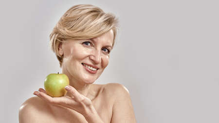 Beautiful middle aged woman smiling at camera while holding green apple, posing isolated over grey background 免版税图像 - 159195836