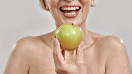 Close up of hand of middle aged woman smiling while holding green apple near her mouth, posing isolated over grey background
