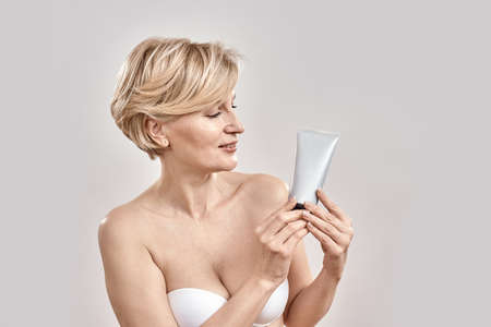 Beautiful middle aged woman holding and looking at cosmetic skincare bodycare product while posing isolated over grey background 免版税图像 - 159195604