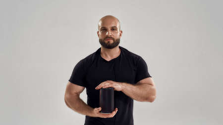 Young muscular caucasian man holding whey protein bottle