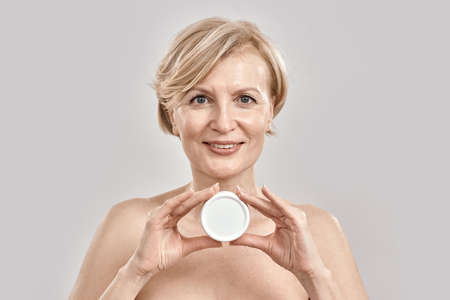 Portrait of beautiful middle aged woman smiling at camera, holding moisturizing facial cream while posing isolated over grey background 免版税图像 - 159139294