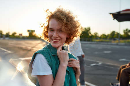 A close up of a well-dressed redhead curly young woman with freckles smiling standing looking into a camera outside on a parking site with her friends on a background