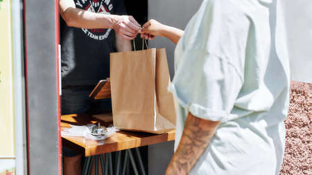 Cropped shot of woman taking paper bag with her order from hands of shop assistant while collecting her purchase from the pickup point Stock fotó