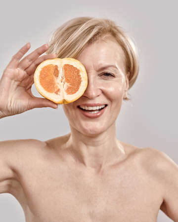 Close up portait of beautiful middle aged woman smiling at camera while holding half of orange in front of her eye, posing isolated over grey background