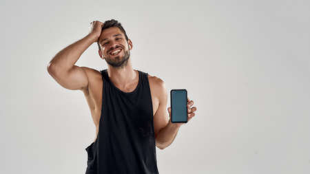 Young handsome caucasian trained man holding smartphone