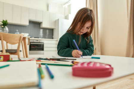 A small girl writing notes sitting alone at a table in a big bright kitchen 免版税图像 - 159139305