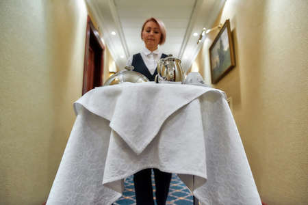 A service so desirable. Waitress walking along the hall while delivering tray with food in a room of hotel. Room service. Focus on table 免版税图像 - 159139308