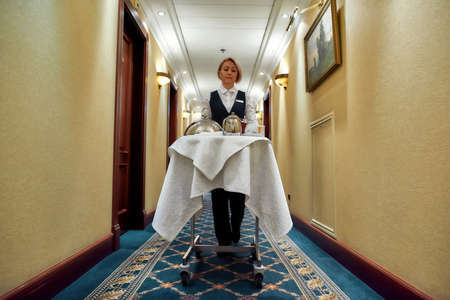 Feel the class. Full-length shot of waitress walking along the hall while delivering tray with food in a room of hotel. Room service.