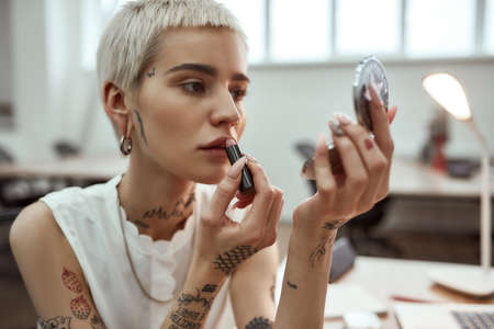 Doing make up. Portrait young and attractive blonde tattooed woman applying lipstick while sitting in the modern office 免版税图像 - 159139310