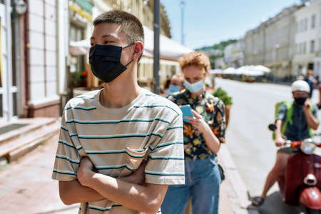 Young asian guy wearing mask waiting in line, respecting social distancing to enter takeout restaurant or to collect purchases from the pickup point during coronavirus lockdown 免版税图像 - 159139312